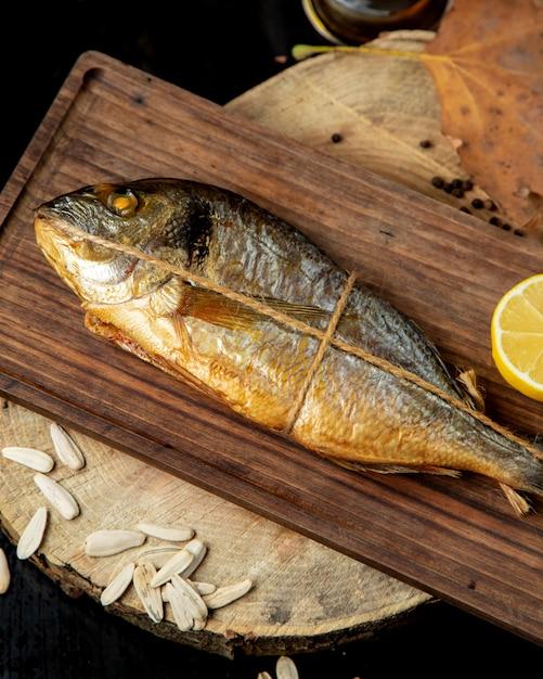 Рыба вяленого копчения, завернутая в веревку, подается с половиной лимона на деревянной доске Бесплатные Фотографии