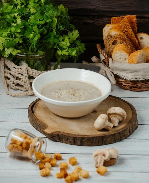 きのこのスープは木製のサービングボードにパンの詰め物を添えて 無料写真