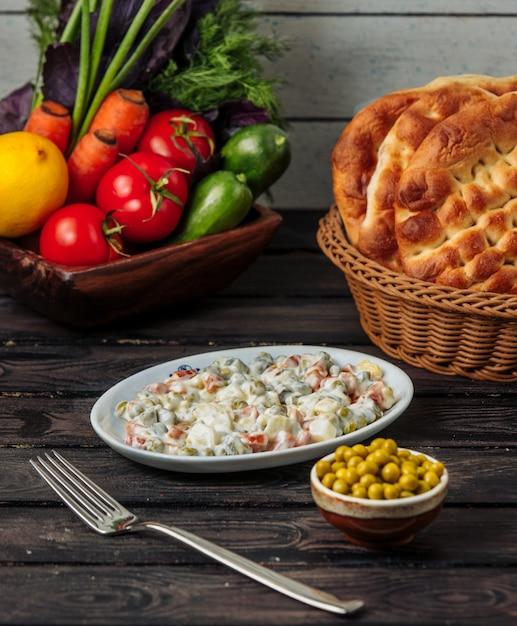 白い小皿のオリビエサラダ、グリーンピース添え 無料写真
