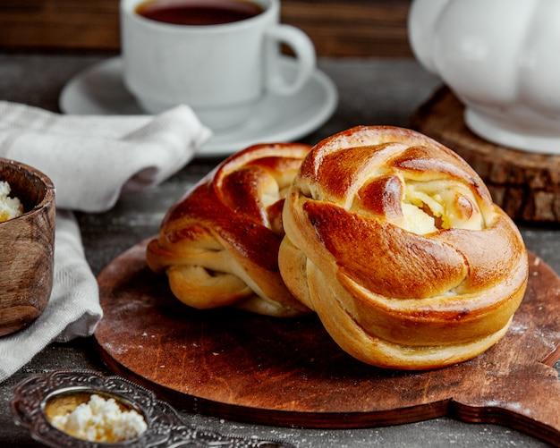 木製のサービングボードで提供されるバラの形の甘いパン 無料写真