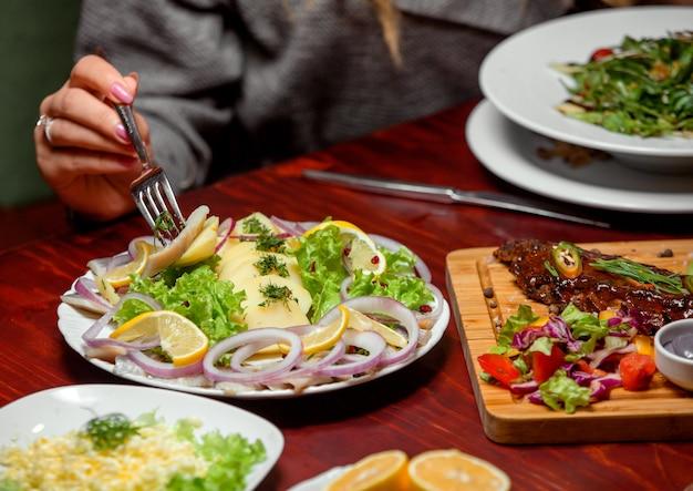 Кусочки рыбы с зеленью лука и лимона Бесплатные Фотографии