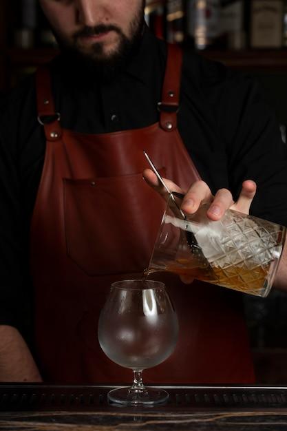 クリスタルガラスから飲み物をスニフターに注ぐバーテンダー 無料写真