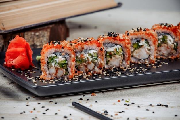 エビ、キュウリ、赤いトビコで覆われた巻き寿司のクローズアップ 無料写真