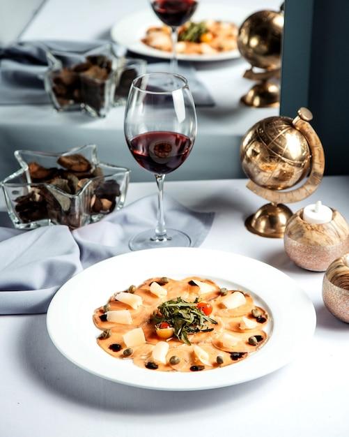 魚のスライスチーズとグラスワイン 無料写真