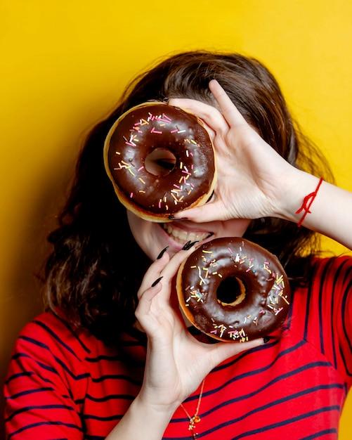 チョコレートとドーナツのペアを保持している女性 無料写真