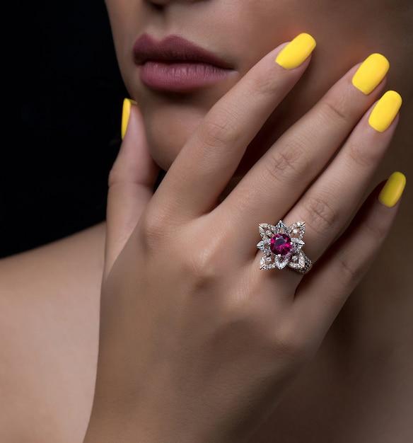 白とブルゴーニュの石の花の形のダイヤモンドリングを持つ女性の手 無料写真