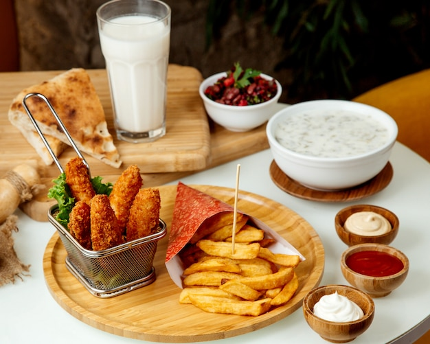 Картофель фри и куриные наггетсы в кляре на деревянной доске Бесплатные Фотографии