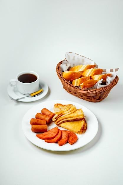 揚げソーセージソーセージとパンケーキプレート黒茶と朝食の朝食 無料写真