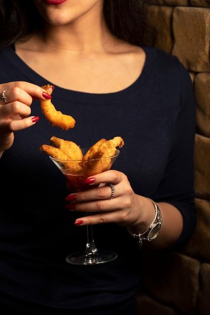 女性は甘いチリソースで揚げたエビカクテルのグラスを保持しています。 無料写真
