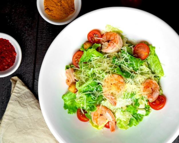 レタスパルメザンチェリートマトとパン詰めのエビシーザーサラダ 無料写真