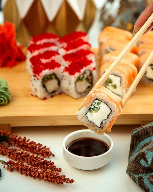 スモークサーモンキュウリとクリームを添えた巻き寿司 無料写真