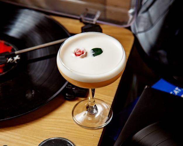 Стакан пенного коктейля, украшенного цветами и листьями Бесплатные Фотографии