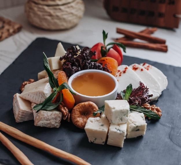 テーブルの上の蜂蜜とチーズプレート 無料写真