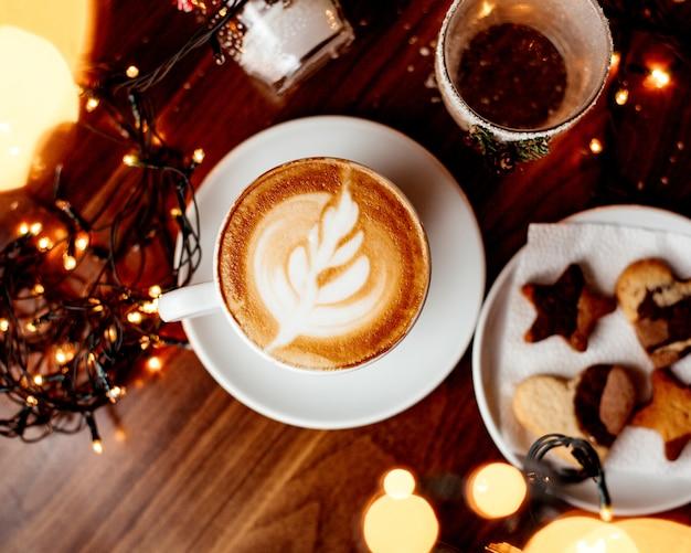 ホットカプチーノのカップとクッキートップビューでプレート 無料写真