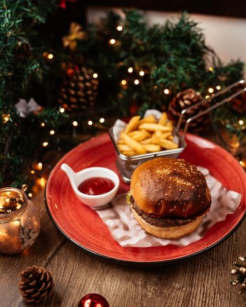 Вид сверху говядины бургер подается с картофелем фри кетчуп уха рождественские украшения Бесплатные Фотографии