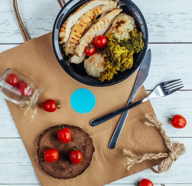 ブロッコリーと木の板にトマトのフライドチキン 無料写真