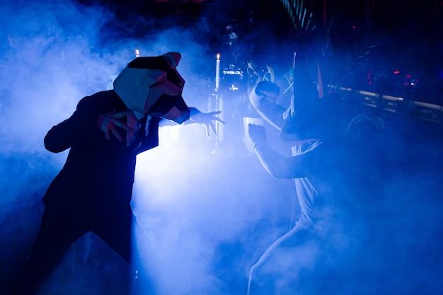 Двое мужчин в масках животных позируют на вечеринке в клубе Бесплатные Фотографии
