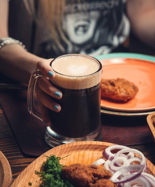 テーブルの上のフライドチキンとマグカップで黒ビール 無料写真