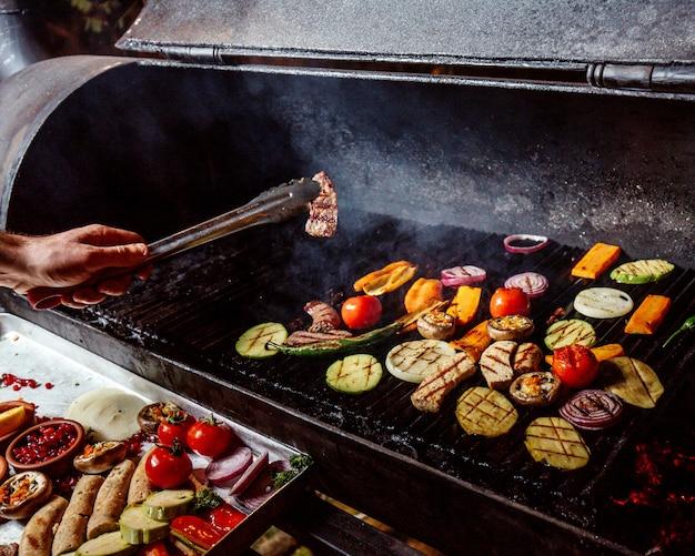 Мужчина жарит овощи на гриле с колбасками Бесплатные Фотографии