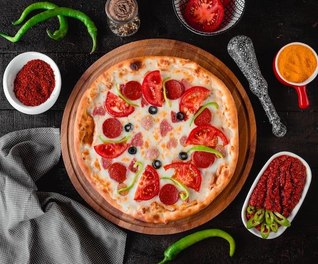ソーセージトマトとオリーブのトップビューのピザ 無料写真