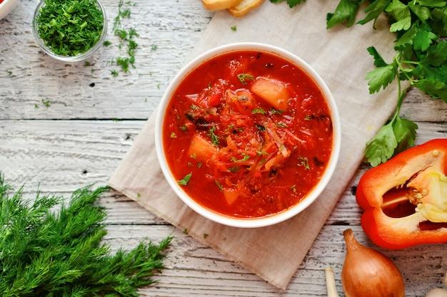 赤いトマトのスープ。ウクライナ語とロシア語のボルシチ。白い木製のテーブルに白いボウルのボルシチ。 Premium写真