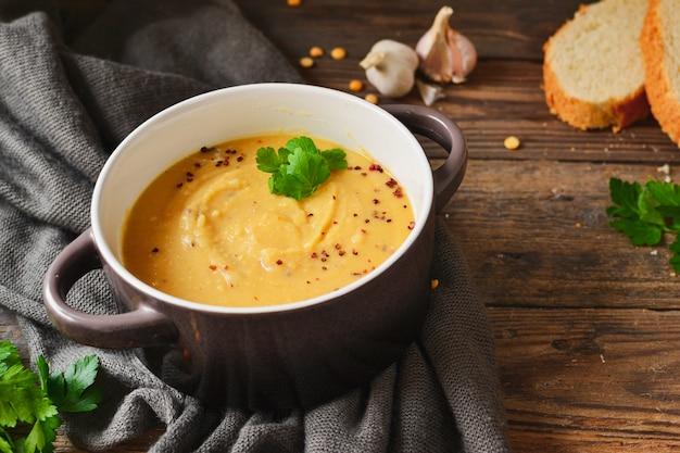 木製のテーブルの上にボウルにエンドウ豆のクリームスープ。エンドウ豆のピューレとお粥。 Premium写真