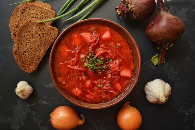 ウクライナ料理とロシア料理。黒い表面に赤いボルシチ。ボルシチと野菜とトマト。ビート、玉ねぎ、パン、トマト、キャベツ、ニンニク。 Premium写真