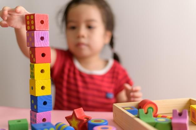 Маленькая курчавая азиатская девушка наслаждается сыграть при деревянные блоки игрушки изолированные на белой стене. концепция образования и обучения. Premium Фотографии
