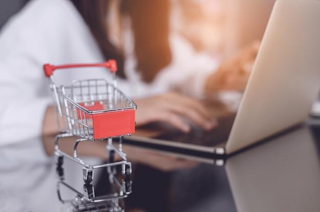 タブレット画面のトロリー。オンラインショッピングに関するアイデア、女の子は電話を使用してインターネット経由で売り手から商品を直接購入します。オンラインショッピング中毒のコンセプト Premium写真