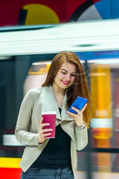 Молодая женщина возле метро, глядя на смартфон Premium Фотографии