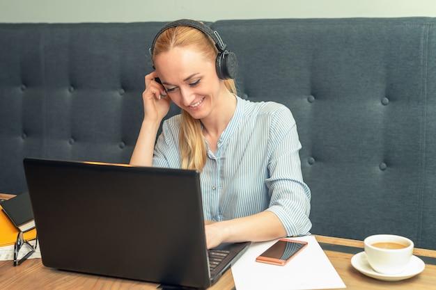 ヘッドフォンを着用し、オフィスのテーブルで開いているラップトップの前に座っている笑顔の若い女性 Premium写真