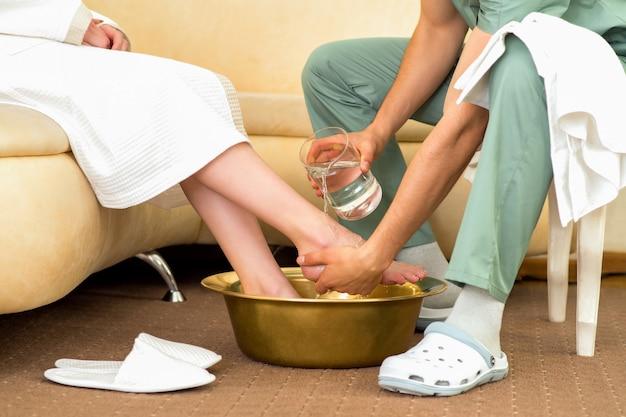 マッサージセラピストが女性の足をマッサージサロンで洗います。 Premium写真