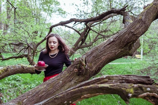 木の幹の近くに立っている女の子 Premium写真