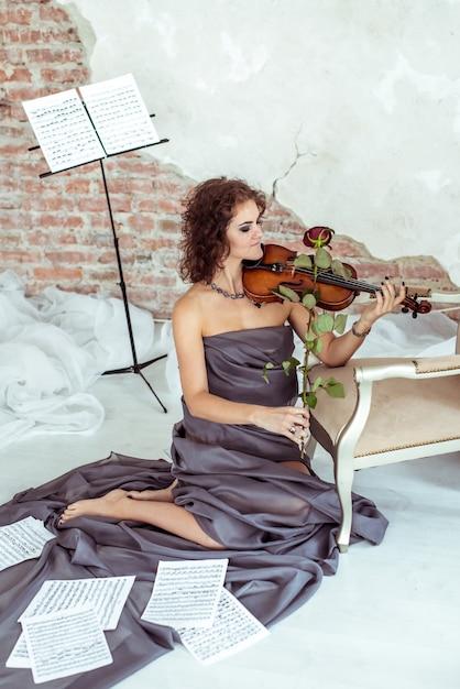バイオリンの弓のバラを演奏する美しい女性 Premium写真