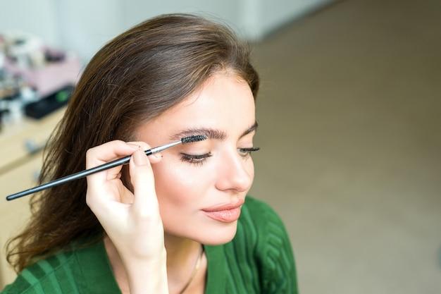 Женщина красит брови Premium Фотографии