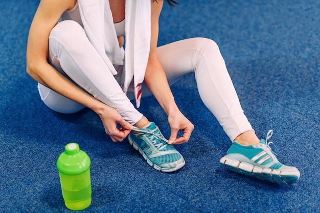 Красивая спортивная женщина с идеальным телом завязывает шнурки на кедах в спортзале Premium Фотографии