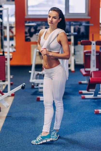 Молодая красивая спортивная женщина с совершенным телом делает тренировки в тренажерном зале Premium Фотографии