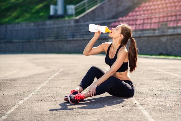 Фитнес бегун женщина питьевой воды или энергетический напиток из спортивной бутылки Premium Фотографии