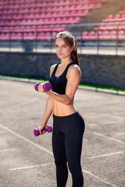 スタジアムで紫外線ダンベルでトレーニングを行う完璧なボディを持つ美しいフィットネス女性 Premium写真