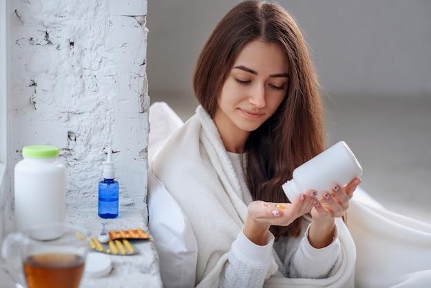 Женщина разлив лекарства, таблетки и капсулы на руку Premium Фотографии