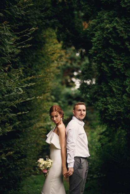 官能的な美しい花嫁とハンサムな新郎がお互いに戻って横になっています。 Premium写真
