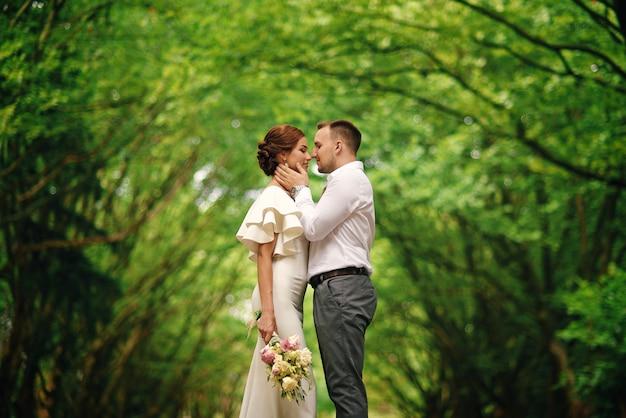 Стильная милая пара в теплых объятиях под аркой деревьев в парке Premium Фотографии