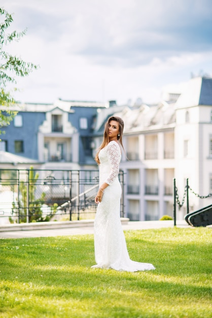 Привлекательная очаровательная невеста в белом кружевном платье на зеленой траве Premium Фотографии