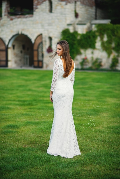 Привлекательная очаровательная невеста в белом кружевном платье на зеленой траве на стенах замка Premium Фотографии