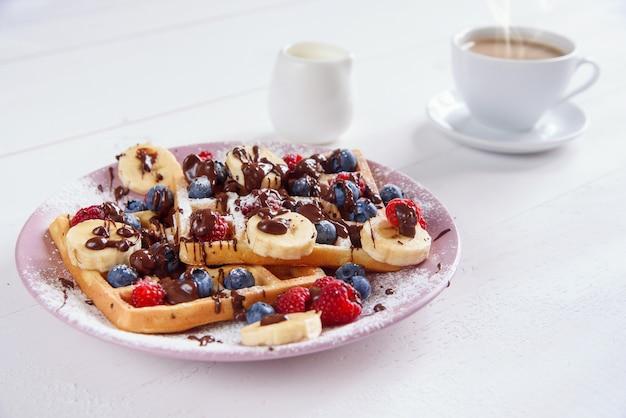 一杯のコーヒーとブルーベリー、ラズベリー、バナナ、砂糖の粉が入ったおいしいベルギーワッフルには、液体チョコレートが入っています。 Premium写真