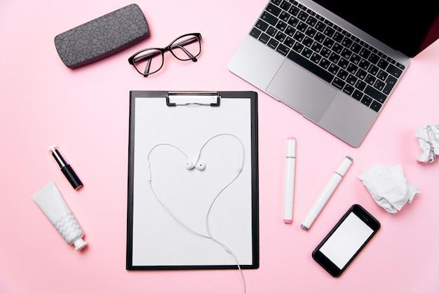 オフィス愛の概念。ハートのようにレイアウトされたヘッドフォン付きの女性のピンクのオフィスデスク。ノートパソコン、空白の白い画面、クリーム、口紅、眼鏡、消耗品と電話で女性の職場。 Premium写真