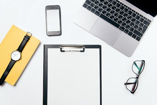 Стол офиса взгляд сверху белый с компьтер-книжкой, телефоном, тетрадью, чистым бланком бумаги с космосом бесплатной копии и поставками, плоской предпосылкой положения. Premium Фотографии