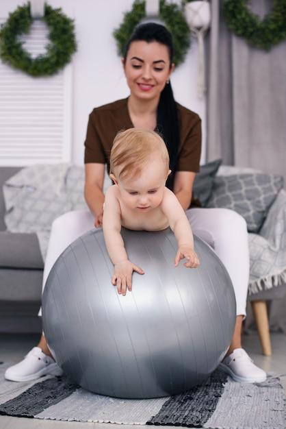 医療室で体操のボールで演習を行って幸せな赤ちゃんと理学療法士。医療と医療のコンセプト。 Premium写真