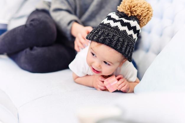 かわいい幼児は青いソファに横たわって、幸せな若いママが彼の足をこねて幸せにします。 Premium写真