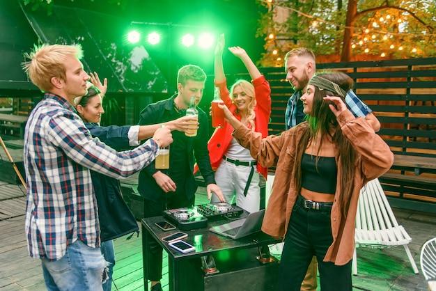 ビールを飲み、音楽に合わせて踊り、チャットし、屋外の夏のパーティーで良い休憩時間を過ごしている友人のグループ。 Premium写真